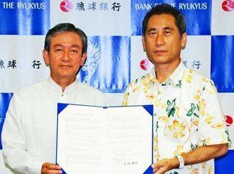 連携協定を結んだ琉銀の金城頭取(左)と琉大の仲座機構長=4日、那覇市・琉銀本店