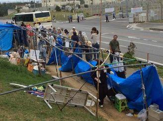 台風対策でテントを片付ける辺野古新基地建設に反対する住民ら=11日午前、名護市辺野古のキャンプ・シュワブ前