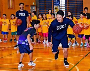 1対1で小学生と対戦するキングスの田代直希(手前右)と新城真司(同3人目)=南城市・船越小学校体育館