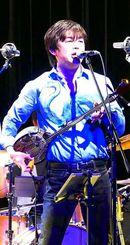 ギターを三線に持ち替えて「島唄」を歌う宮沢和史=沖縄市・ミュージックタウン音市場
