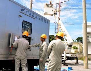 高圧発電機車からの送電を訓練する社員=21日、浦添市・沖縄電力本店