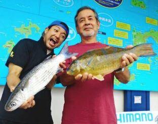 奥海岸の地磯で41.5センチ、1.22キロのアーガイを釣った安里幸男さん(右)=9日
