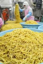 ゆでた麺に油をなじませ、冷やす作業に追われる従業員=30日、糸満市西崎町・サン食品
