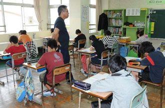 教師から説明を受けた後、テストに臨む児童ら=22日午前8時40分、那覇市・与儀小学校