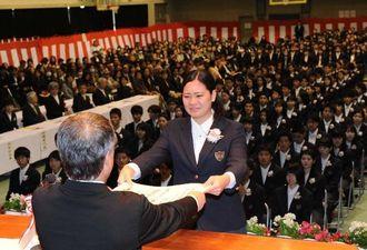 涙ぐみながら卒業証書を受け取る生徒=1日午前10時40分ごろ、浦添市大平・陽明高校