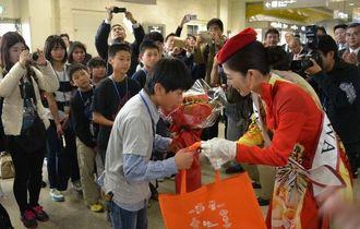 ミス沖縄の新里由香さんから花束を受け取る神戸の子どもたちら=9日、那覇空港