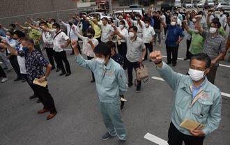 新型コロナウイルス感染対策のため、マスクをして互いに距離をとりながら、出陣式でガンバロー三唱する支持者=29日午前、本島内