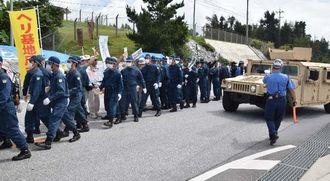 米軍車両の通行を阻止しようとする市民らを排除する県警機動隊員ら=24日午前、名護市辺野古の米軍キャンプ・シュワブのゲート前