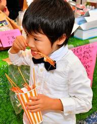 車エビをおいしそうに食べる子ども=8日午後、那覇市久茂地・タイムスビル