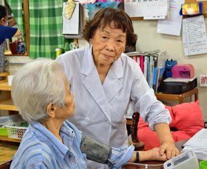 利用者の血圧を測定する仲井間小夜子さん=7月27日、沖縄市・デイサービスセンターエデンの園(写真撮影のためマスクを外しています)