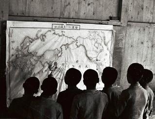 「糸満人の分布図」を見る子どもたち。糸満小の創立80周年記念誌(1964年)によると、展示場所と見られる同小「郷土会館」は「戦争で灰燼に帰した」。金城光栄さんが証言したガラスケース入りの銃について、沖縄国際大教授の吉浜忍さん(67)は現在の読谷村の忠魂碑でも展示用の砲弾を在郷軍人会から海軍省に求め、飾ったいきさつがあることから「当時は沖縄に常駐していなかった軍隊に親近感を抱かせるため、提供する制度が学校向けにもあったのではないか」とみる(写真は朝日新聞提供)