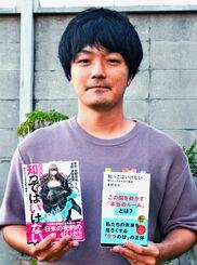 漫画版「知ってはいけない」と原作を手にする伊佐義勇さん=25日、うるま市の自宅