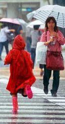沖縄地方が梅雨入りし、雨の中、足早に横断歩道を渡る通行人=20日午後3時55分、那覇市久茂地(長崎健一撮影)