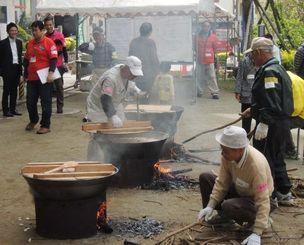 地震や津波を想定した訓練で豚汁をつくる人たち。大きな白い紙(中央奥)には、気づいた問題点が書き込まれていた=那覇市の繁多川公民館