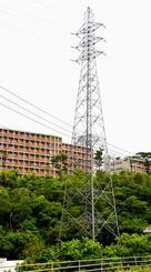 高さ制限超過で移設が決まった沖縄電力の送電鉄塔。約80メートルの距離にある沖縄高専の学生寮(後方)は適用除外とされた=名護市辺野古