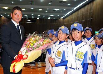所属していた少年野球チームの後輩から、花束を受け取る嶺井博希さん=南城市玉城の中央公民館