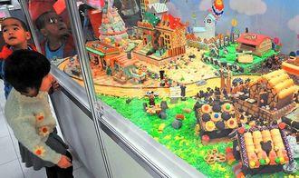 お菓子で作られた街に見入る子どもたち=13日、那覇市・リウボウ