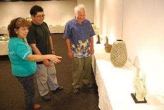 展示作品を前に談笑する新垣修さん、寛さん、初子さん(右から)=4日、那覇市久茂地・タイムスギャラリー