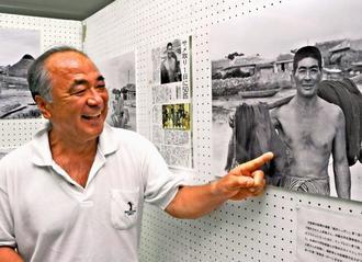 祖父・上原亀さんの顔を初めて見た勝さん。「サメトヤー(サメ漁師)だったのも、記事を見て初めて知った」。家筋の通称「三男仁王(ニワー)ヤー」に、祖父のあだ名「仁王」が息づいている=22日、糸満市役所