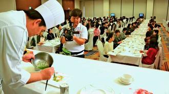 マダイのカルパッチョを盛り付ける今村建一副総料理長(左)=15日、糸満市のサザンビーチホテル&リゾート沖縄
