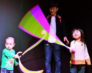 ロープを回すと現れる虹色の残像に驚きの表情を見せる子どもたち=17日午後、北中城村・イオンモール沖縄ライカム
