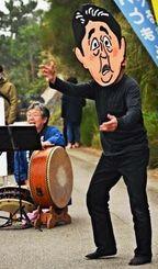 辺野古新基地建設について表現した面踊りを披露する「花こま」の団員=24日、名護市辺野古