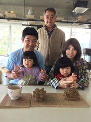 4歳と2歳の子どもを抱く内間安路さん(左)と妻の智美さん(右)。中央は内間さんの父安則さん=2014年12月、読谷村内(提供)