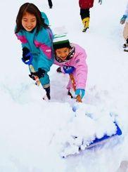 スコップで雪をかく。想像以上の重さに驚きの声が上がった=大蔵村清水・大蔵小学校校庭