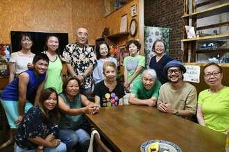 常連客らに囲まれ笑顔を見せる店主の國場清玉さん(前列中央)=10日、沖縄市中央の台湾料理店「凱莎琳(キャサリン)」