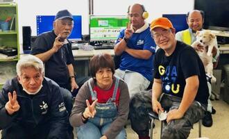 助成金で購入したパソコンを前に笑顔を見せる利用者ら=沖縄市(提供)