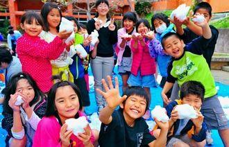 福島の雪だるま親善大使・古川萌々さん(後方中央)から贈呈された雪を手に、大はしゃぎする馬天小3年の児童たち=5日、南城市の同校