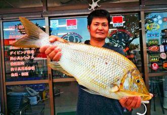 西崎一文字で67センチ、3.69キロのタマンを釣った仲村渠康さん=7月23日