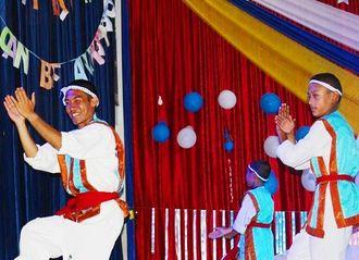 カーテンで作ったウッチャキを着てスクールコンサートで子どもたちと一緒に鳩間節を踊る比嘉航也さん(左)=ブータン