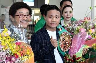 花束を手に記念撮影に収まる世界フライ級王者の比嘉大吾(中央)と具志堅用高会長(左)=9日午前、那覇空港