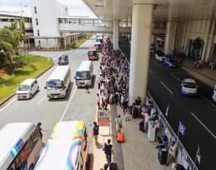 観光客送迎のためレンタカー用の送迎車で混雑する那覇空港国内線ターミナル前=2017年8月、那覇市