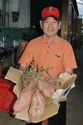 約10キロのサツマイモの収穫を喜ぶ當眞嗣盛さん=宜野座村松田区