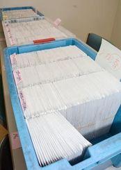 返送順に番号を振られて整理された、マイナンバー通知カードの入った簡易書留の束=那覇市役所