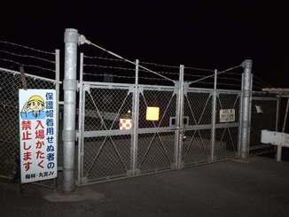 米軍キャンプ・ハンセン内の安富祖ダム工事現場のゲート前。工事車両や水タンクを米軍の流れ弾が傷付けたとされる=14日午後8時53分、沖縄県恩納村安富祖
