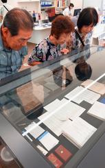 故大田昌秀さんの自筆原稿や遺品に見入る来館者たち=12日、那覇市の県立博物館・美術館
