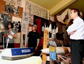 阿波根昌鴻さんの解説音声を聞きながら展示を見る関係者=4日、伊江村・ヌチドゥタカラの家