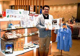「通販生活」に掲載した沖縄と福島の応援企画をアピールするカタログハウスの関根理編集部ゼネラルマネージャー。同社のショップでも商品を販売している=14日、東京都渋谷区の同社