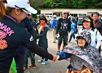 最終日のスタート直前、大城さつき選手と握手を交わす父の良雄さん(右)と、車いすを押す母のコズエさん(奥)=5日、南城市の琉球GC