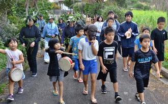 「パーントゥ」に扮した男児を先頭に集落内の厄をはらう住民たち=23日夕、宮古島市上野野原