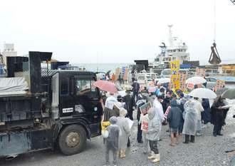 辺野古新基地建設用の砕石を搬入するダンプカーの前に立ちはだかり、新基地建設に抗議する市民ら=4日、本部港塩川地区