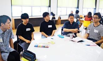 学生と沖縄の労働問題を話し合うケント・ウォン所長(右から2人目)=22日、那覇市の沖縄大学