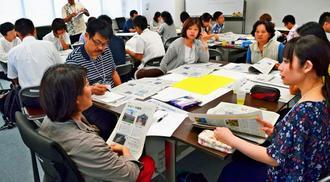 本紙子ども向け新聞「ワラビー」などの沖縄戦特別版を使った授業案を考える教師=17日、那覇市・琉球新報社