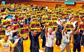陸自配備に反対するプラカードを掲げ、中山義隆市長の受け入れ表明に抗議する市民ら=29日、石垣市総合体育館