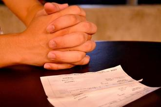 返済額が記された明細書を前に手を組むカイさん。「何よりも、お金を返してほしい」と訴える