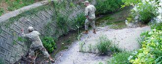 クラサク川を見回る米軍関係者=18日午後6時48分、沖縄市知花