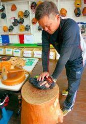 湯につけて柔らかくしたグローブをもみ型をつくる喜久山さん=うるま市江洲